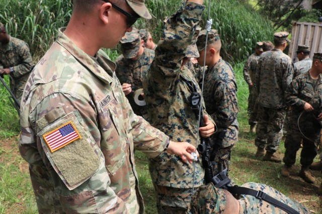 1st. Lt. Grant Grainger, a platoon leader with 95th Clearance Company, 84th Engineer Battalion inspects a uli knot charge fabricated by Marines from Combat Assault Company, 3rd Marine Regiment June 7th, 2018.