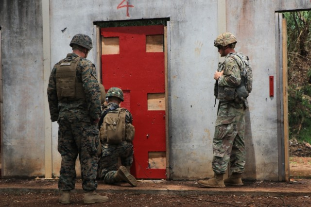 Gunnery Sgt. Justin Skelly from Combat Assault Company, 3rd Marine Regiment, and 1st. Lt. Grainger from 95th Clearance Company, 84th Engineer Battalion observe as a Marine assigned to Combat Assault Company of the 3rd Marine Regiment  places a donut charge on a fabricated door during a demolition exercise on June 7th.