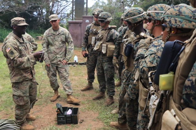 Sgt. Jordan Merchant from 95th Clearance Company, 84th Engineer Battalion teaches Marines from Combat Assault Company, 3rd Marine Regiment on the use of a timed-fuse delay.