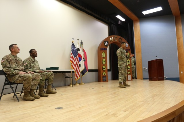 CAMP RED CLOUD, Republic of Korea -- Guest speaker, Sgt. Maj. Gabriel Camacho, 2nd Infantry Division ROK-U.S. Combined Division surgeon sergeant major, addresses the graduates of Battle Staff Noncommissioned Officer Course 16-18 during the commencement ceremony held at the installation theater June 28. Sgt. 1st Class Kenneth J. Meckel, 2ID/RUCD communications noncommissioned officer, recognized as best assistant instructor sits on the far left of the stage and Sgt. Maj. Tommie L. Jones, 2ID/RUCD logistics sergeant major, in charge of orchestrating the establishment of the course for 2ID/RUCD, observe the commencement ceremony which marked the completion of the first-ever 2ID/RUCD Battle Staff NCO Course.