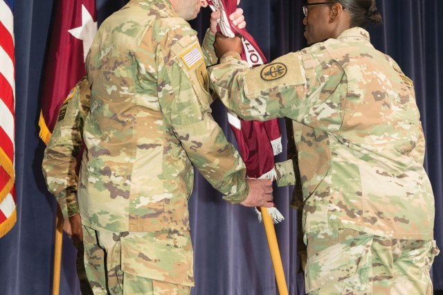 Brig. Gen. Telita Crosland, commanding general, Regional Health Command-Atlantic, passes the Warrior Transition Battalion-Fort Belvoir guidon to Lt. Col. Joseph Messina, incoming commander, during change of command ceremony June 22 on Fort Belvoir.