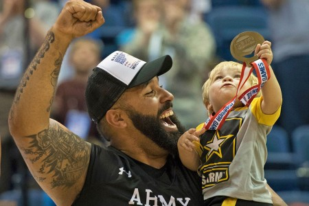 Sgt. Chris McGinnis and his 17-month-old son celebrate Army's gold medal in wheelchair basketball, the final event of the 2018 DOD Warrior Games at the U.S. Air Force Academy, Colorado Springs, June 9, 2018. The Warrior Games are an annual event, established in 2010, to introduce wounded, ill and injured service members to adaptive sports as a way to enhance their recovery and rehabilitation.