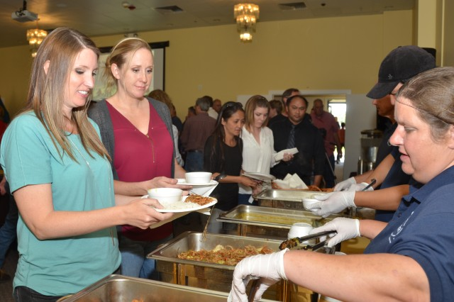 Kelcie Reed (left) and Stacy Youngren stand in line at tasting table at the Asian American/Pacific Islander Heritage Month Observance, June 14, 2018, at the Dugway Community Club prepared by staff members. Photo by Bonnie A. Robinson, Dugway Public Affairs.