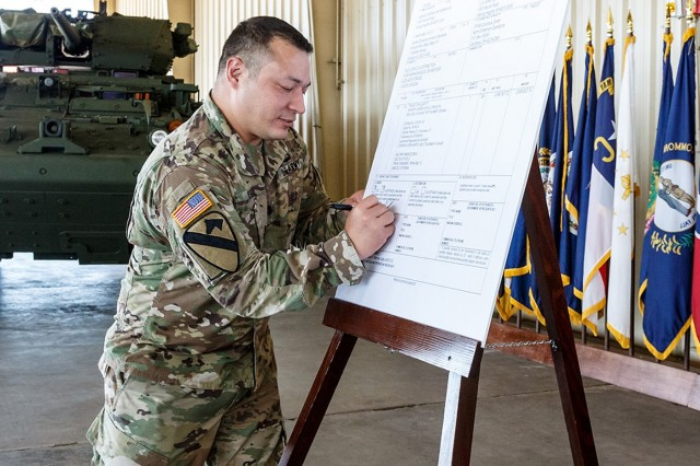Lt. Col. Joseph Rosen, product manager for Stryker Future Operations, signs the DD250 form for the final Stryker Infantry Carrier Vehicle Dragoon vehicle in the initial production run.