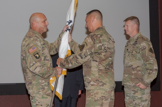 Lt. Col. Travis Harris, left, accepts the project office flag from Col. Roger Kuykendall, the Aviation Turbine Engines project manager, in accepting responsibility as the product manager of the Improved Turbine Engines program from Lt. Col. Curt Kuetemeyer, right, during a change of charter ceremony June 18 in Bob Jones Auditorium.