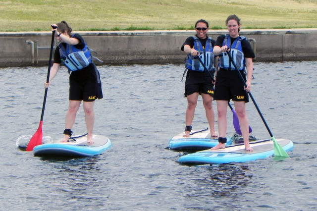 Three medical officer students partake in one of Fort Sill's Family, Morale, Welfare and Recreation's paddle board lessons June 24, 2018 at Lake Elmer Thomas Recreation Area. From left: 2nd Lt. Rebecca Porter, 2nd Lt. Neda Othman, and 1st Lt. Heather Fischle.
