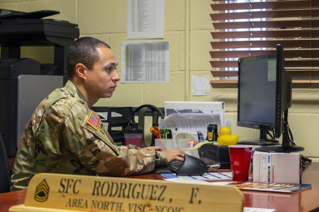 Sgt. 1st Class Francisco Rodriguez, the NCOIC of the Visual Information Support Center at Camp Casey, South Korea, works at his desk May 29, 2018, before a lunchtime workout he often conducts alongside his Soldiers. Rodriguez leads the group that performs multiple fitness sessions each duty day in an effort to improve readiness and stay physically fit.