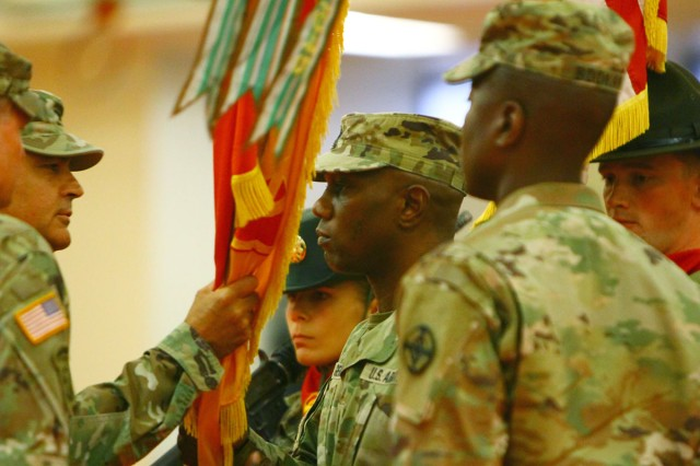 Col. Jeffrey Buck, 428th FA Brigade commander, hands the brigade colors to Command Sgt. Maj. Gerry German (center) to signify his acceptance of responsibility as the new brigade CSM June 22, 2018, at Rinehart Fitness Center.