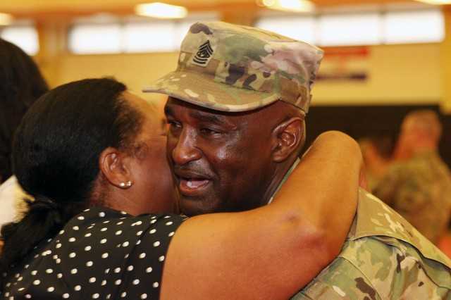 Outgoing Command Sgt. Maj. Kenneth Oliver gets a hug from a well-wisher after the ceremony. Oliver moves on to Shaw Air Force Base, S.C., where he will be a liaison with the 4th Battlefield Coordination Detachment.