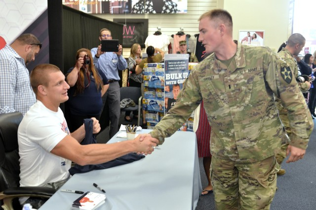 Two-time Super Bowl Champion, Rob Gronkowski, All-Pro tight end for the New England Patriots, shakes hands with 1st Lt Ryan Gibley Ryan, of 2-2 Stryker Brigade Combat Team, 7th Infantry Division, during a signing event held June 27 at the Lewis Main Exchange. Gronk signed shirts, footballs and other items while taking photos with those who attended. (U.S. Army photo by Staff Sgt. Chris McCullough)