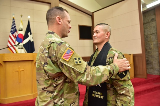 CAMP RED CLOUD, Republic of Korea - Chaplain (Lt. Col.) Hyeonjoong Kim, incoming 2nd Infantry Division ROK-U.S. Combined Division command chaplain receives the stole from presiding officer, Maj. Gen. D. Scott McKean, 2ID/RUCD, commanding general signifying transfer of command chaplain responsibility during the Change of Stole Ceremony held at the Warrior Chapel June 21. (U.S. Army photo by Mr. Pak Chin U. 2ID/RUCD Public Affairs)