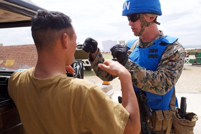 U.S. Marine Corps Lance Cpl. Tanner Yeager, B Company, 3rd Law Enforcement Battalion, talks with a simulated civilian resident June 20, 2018, during Khaan Quest 2018 entry control point operations training at Five Hills Area, Mongolia. The purpose of Khaan Quest is to gain U.N. training and certification for the participants through the conduct of realistic peace support operations, to include increasing and improving U.N. peacekeeping interoperability and military relationships among the participating nations.