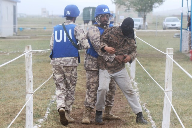 Qatari soldiers attempt to restrain a civilian from running through the distribution site as part of a Khaan Quest 2018 training exercise at Five Hills Training Area June 23.  KQ18 is a regularly scheduled, multinational exercise co-sponsored by U.S. Pacific Command and hosted annually by the Mongolian Armed Forces.  This exercise is the latest in a continuing series of exercises designed to promote regional peace and security.  This year's exercise marks the 16th anniversary of this training event.
