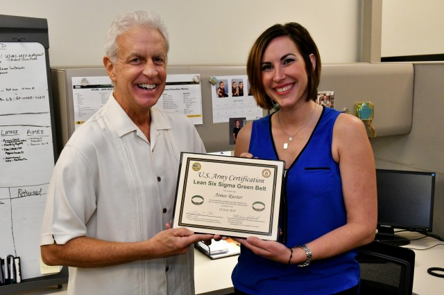 Aimee Riester, a traffic management specialist with the Military Surface Deployment and Distribution Command, receives her Lean Six Sigma Green Belt certification from Tye Beasley, her former supervisor and chief of the International Movements Division.
