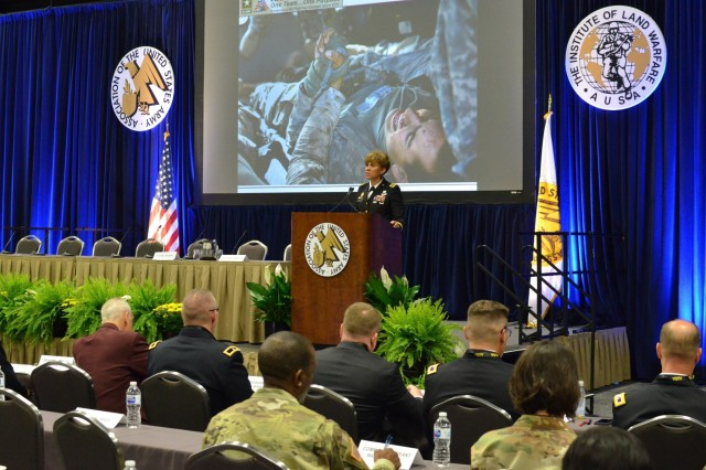 "At the 2018 Association of the United States Army Medical Symposium (MEDAUSA) on June 26-27, in San Antonio, Texas, Lt. Gen. Nadja Y. West, U.S. Army Surgeon General and commanding general, U.S. Army Medical Command, discusses a photo of a soldier being medically evacuated and holding the hand of another injured Soldier for comfort. ""It grabbed me, it shows a soldier getting comfort from his fellow wounded soldier."" said West. This photo is the clearest way for West to explain what Army Medicine does for the Army and emphasizes that we are part of the operation and not just support. (DoD Photo by Wesley Elliott, MEDCOM/OTSG Directorate of Public Affairs, U.S. Army/Released.)"