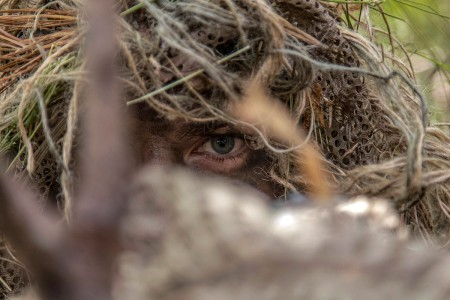 A Special Forces Soldier with the 20th Special Forces Group, Massachusetts National Guard, stalks a target during a reconnaissance and surveillance exercise at Joint Base Cape Cod, Mass., June 8, 2018.