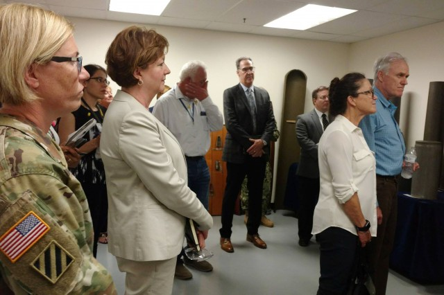 Col. Michelle Letcher, commander, Joint Munitions Command and Lisha Adams, executive deputy to the commanding general, Army Materiel Command, look on as Secretary of the Navy Richard V. Spencer is briefed about the purpose of the Quad City Cartridge Case Facility.