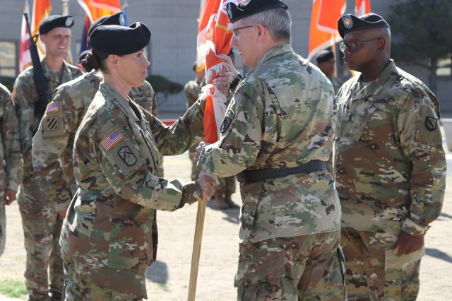 NETCOM Commanding General, Maj. Gen. John Baker (center) passes the NETCOM colors to incoming command sergeant major, Command Sgt. Maj. Jennifer Taylor, during a Change of Responsibility Ceremony held at the NETCOM headquarters, Fort Huachuca, Ariz., June 28.  The outgoing senior enlisted advisor for the command, Command Sgt. Maj. Darris Curry (right) looks on.
