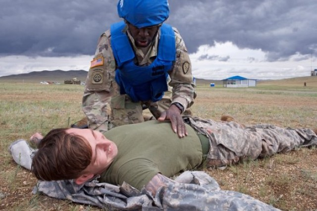 Alaska Army National Guard Spc. Jahmoi Hodge, a member of the platoon representing the 297th Regional Support Group, assesses simulated casualty U.S. Navy Hospital Corpsman 3rd Class John Bustamonte, III Marine Expeditionary Force, June 17, 2018, during Tactical Combat Casualty Care training at Five Hills Training Area, Mongolia, as part of Khaan Quest 2018. The purpose of Khaan Quest is to gain United Nations training and certification for the participants through the conduct of realistic peace support operations, to include increasing and improving UN PKO interoperability and military relationships among the participating nations.  (Photo Credit: Sgt. David Bedard)