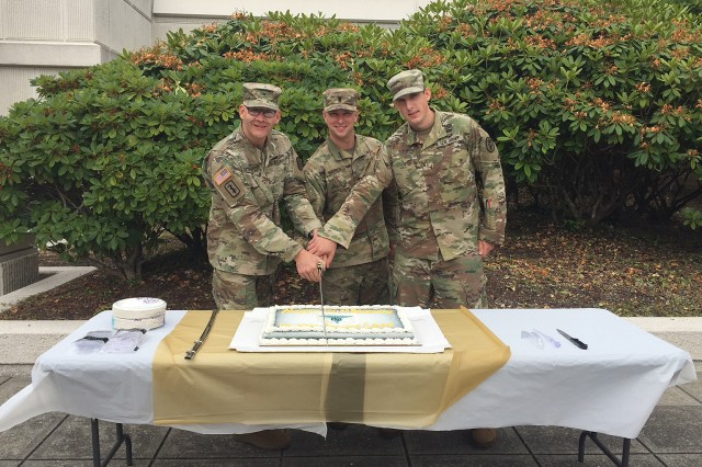 Brig. Gen. Dennis LeMaster, commanding general, Regional Health Command-Pacific, cut a cake alongside the youngest MSC officers in attendance, by age and rank: 1st Lt. Liston Barber, 56th Multifunctional Medical Battalion, 62nd Medical Brigade; and 2nd Lt. Jeremy Todd, C Company, Madigan Troop Battalion, during a June 29 celebration at Madigan Am Medical Center of the 101st Army Medical Service Corps anniversary.