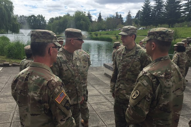 Brig. Gen. Denis LeMaster, commanding general, Regional Health Command-Pacific, and Col. Michael Place, commander, Madigan Army Medical Center, speak to the youngest Medical Service Corps officer, by rank, at the June 29 MSC anniversary celebration at Madigan.