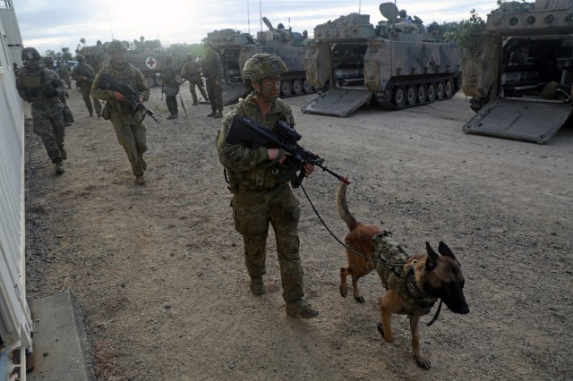 An Australian military policewoman and her canine join U.S. Marines, U.S. Soldiers and Australian Soldiers June 23 in an urban training exercise at Rasberry Creek, as part of Exercise Hamel in Shoalwater Bay Training Area, Australia.