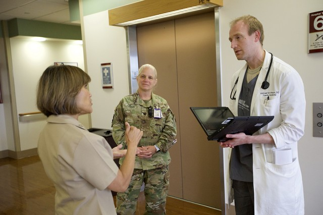 Defense Health Agency Director Navy Vice Adm. Raquel Bono talks with Col. Suzanne Scott, deputy commanding officer, and Maj. (Dr.) Michael Braun, a physician, as they wait for an elevator June 29 at Madigan Army Medical Center on Joint Base Lewis-McChord, Washington.