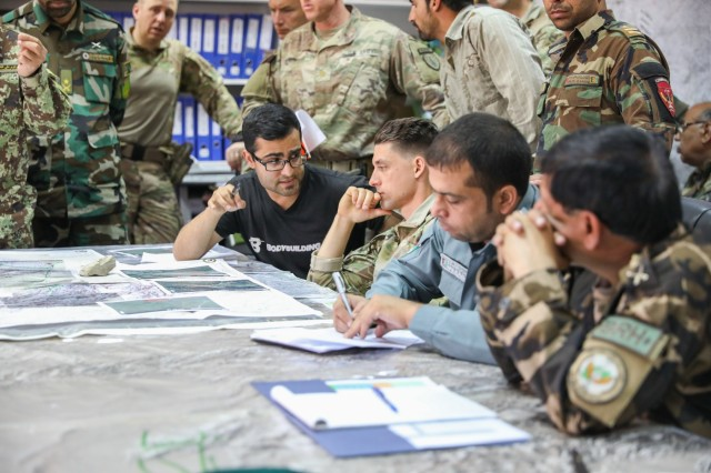 A translator, left, assigned to Train, Advise and Assist Command-South talks to Capt. Brandon Briscoe, center, operations and plans advisor for TAAC-South, May 25, 2018, at Camp Hero in Kandahar, Afghanistan. TAAC-South is a joint Army component command composed of Soldiers from the 40th Infantry Division, California National Guard and the 2nd Infantry Brigade Combat Team, 4th Infantry Division. (U.S. Army photo by Staff Sgt. Neysa Canfield/TAAC-South Public Affairs)