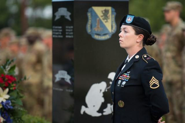 Staff Sgt. Crystal Wenner stands by the Chemical Corps' Global War on Terrorism Memorial during the Sunrise Service held June 28 in Memorial Grove. Four names were recently added to the memorial.