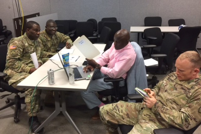 Maj. Michael Keathely observes Staff Sgts. Adebowale Goyea and John Gyaben interact with a role-player vendor, Capt. Tysalaam Bowman, to negotiate the best and final quote aimed at cost savings to a requirement and taxpayer dollars as part of a unit contingency contracting exercise June 28 at Fort Bragg, North Carolina. Keathely is a member of the 922th Contracting Battalion. Goyea and Gyaben are both assigned to the 900th CBN. Bowman is a member of the Mission and Installation Contracting Command-Fort Bragg contracting office.