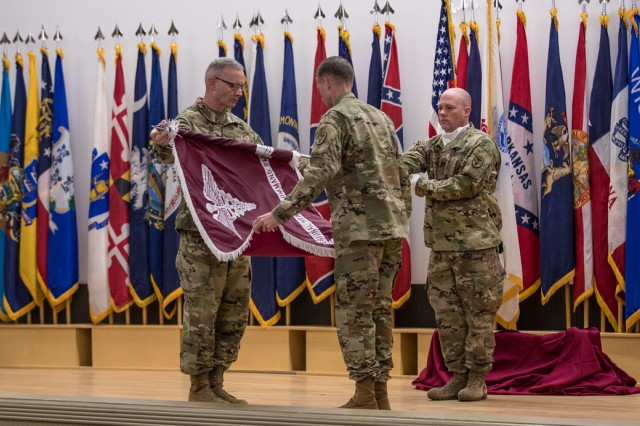 Brig. Gen. Dennis P. LeMaster, left, and Command Sgt. Maj. Clark J. Charpentier, center, command team, Regional Health Command-Pacific, uncase the unit's colors, signifying the movement of the command team from Hawaii to Joint Base Lewis-McChord, Washington, during the Assumption of Responsibility and Uncasing of the Colors Ceremony July 6 at French Theater, JBLM (U.S. Army Photo by John Wayne Liston).