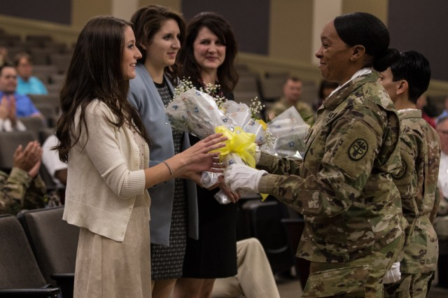 Staff Sgt. Torri Elliott, Regional Health Command-Pacific, second from right, presents flowers to Command Sgt. Maj. Clark J. Charpentier's daughters Maci, left, and Abbi, second from left, after Sgt. Angelique Jefferson, right, presents flowers to Charpentier's wife Mindi, center, during the Assumption of Responsibility and Uncasing of the Colors Ceremony July 6 at French Theater, Joint Base Lewis-McChord, Washington (U.S. Army Photo by John Wayne Liston).