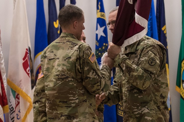 Regional Health Command-Pacific Command Sgt. Maj. Clark J. Charpentier, left, accepts the unit's colors from Brig. Gen. Dennis P. LeMaster, commanding general, RHC-P, right, during the Assumption of Responsibility and Uncasing of the Colors Ceremony July 6 at French Theater, Joint Base Lewis-McChord, Washington (U.S. Army Photo by John Wayne Liston).