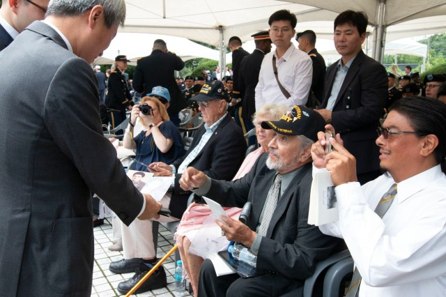 Richard Salazar shares photos of his father, and Task Force Smith member, Sgt. Richard Salazar, Sr., with Osan City Mayor Kwak Sang-wook at the 68th TF Smith Memorial ceremony, July 6. Each year, the city of Osan commemorates the U.S. Soldiers who came to the defense of South Korea, and more specifically, Osan, to block and delay the North's advance as reinforcements were assembled. TF Smith, comprised of a makeshift battalion of the 24th Division, was sent to South Korea to delay the advance of North Korean forces. Inexperienced, understrength and ill-equipped, TF Smith sustained 60 killed, 21 wounded, and 82 captured, during its battle against North Korean forces. Nonetheless, TF Smith delayed the North's advance and reinforcements were eventually able to repel the invasion.
