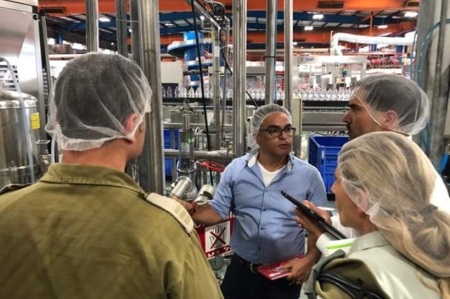 IDF Veterinary Officers and PHA-I Food Safety Officer conduct an inspection of a bottled water facility. From left to right: CPT Shelly Einav, food facility manager, MAJ Evelyn Panzer, CW2 Abraham Montemayor