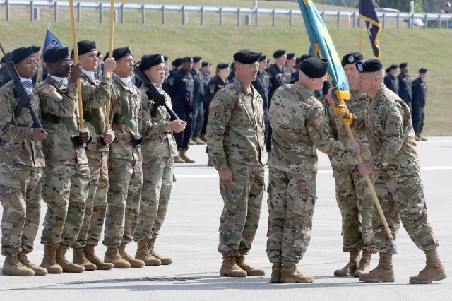 Brig. Gen. Christopher C. LaNeve, 7th Army Training Command's commander, passes the guidon representing the Joint Multinational Readiness Center to the incoming commander, Col. Joseph E. Hilbert, at JMRC's change of command ceremony at the Hohenfels Training Area, Hohenfels, Germany, July 10, 2018. The change of command ceremony is a tradition that represents a formal transfer of authority and responsibility from the outgoing commander to the incoming commander.