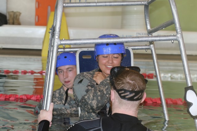 Sgt. Tiffany Pineda, Company C, 2nd General Support Aviation Battalion, 4th Aviation Regiment, 4th Combat Aviation Brigade, prepares to submerge during a Helicopter Underwater Escape Training at Iron Horse Sports and Fitness Center's indoor pool April 24, 2018.