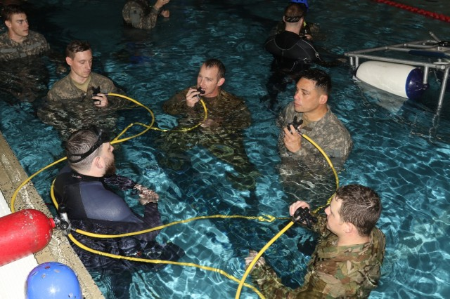 Pilots and crews with the 4th Combat Aviation Brigade learn how to breathe compressed air using a scuba during Helicopter Underwater Escape Training at the Iron Horse Sports and Fitness Center's indoor pool April 24, 2018.