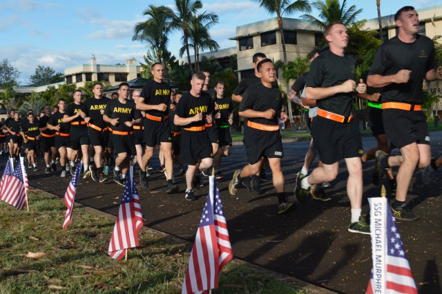 """Soldiers assigned to the 2nd Battalion, 27th Regiment, 3rd Infantry Brigade Combat Team, """"Broncos,"""" 25th Infantry Division, run past Desiderio Field during the Bronco Memorial Run May 25, 2017, at Schofield Barracks, Hawaii. Capt. Reginald B. Desiderio was a company commander assigned to the 27th Inf. Regt. in 1950 and earned the Medal of Honor during the Korean War."""
