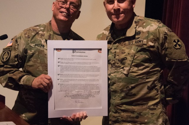 Lt. Gen. Michael A. Bills, Eighth Army commanding general, stands with Chief Warrant Officer 5 Robert Pitts, senior ordinance logistics officer with the Materiel Readiness Division at Eighth Army, as he displays the signed 100th year proclamation in celebration of 100 years of the U.S. Army Warrant Officer Corps at the Post Theater, U.S. Army Garrison Camp Humphreys, South Korea, July 10.