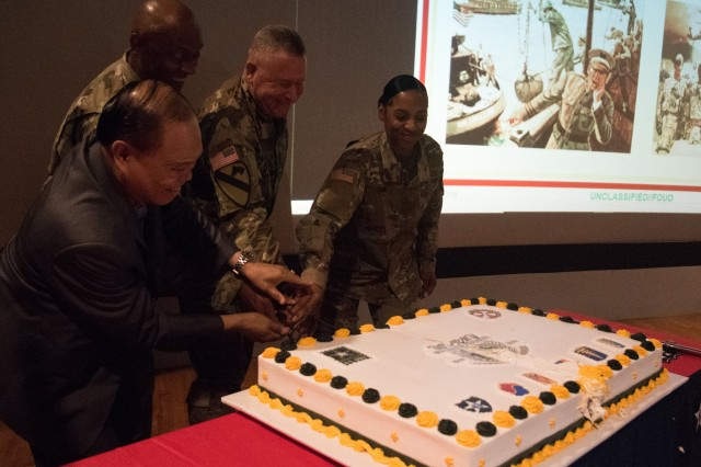 Lt. Gen. Michael A. Bills, Eighth Army commanding general, cuts the cake in celebration of 100 years of the U.S. Army Warrant Officer Corps, alongside Chief Warrant Officer 5 (Retired) Atelano Villon and the youngest and oldest warrant officers present at the Post Theater, U.S. Army Garrison Camp Humphreys, South Korea, July 10. More than 250 Warrant Officers gathered together to celebrate and recognize the 100th birthday of the Army Warrant Officer Corps.