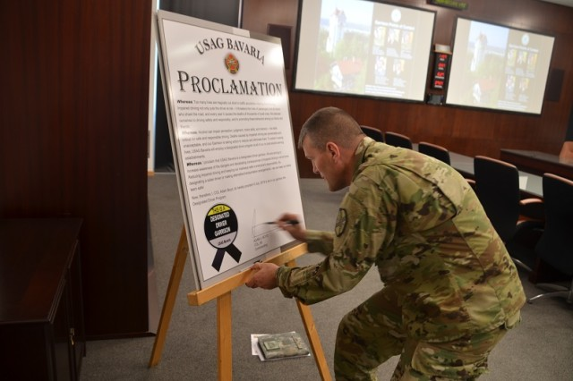 Col. Adam J. Boyd, commander of U.S. Army Garrison Bavaria, signs the Designated Driver Program Proclamation, here, July 9 as part of the ongoing effort to reduce alcohol related incidents throughout the community.