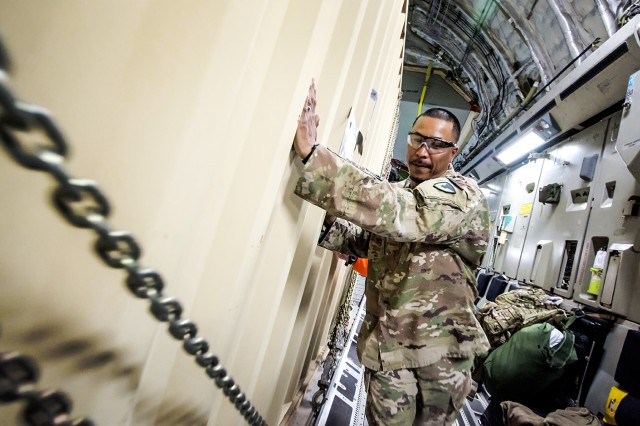 George Barnes, traffic management specialist, Army Field Support Battalion-Afghanistan helps the load crew download a container from a C-17 Globemaster III at Bagram Airfield, Afghanistan, March 14, 2018.