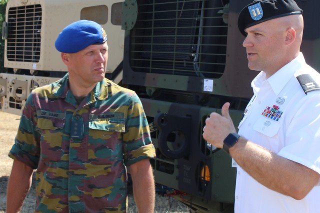 Col. Filip De Vare (left), chief, Section Land Systems, of the Belgium Army's Directorate General Material Resources listens to Capt. Hans Mogelgaard, operations officer APS-2 Zutendaal in front of a heavy equipment transport system at Army Preposition Stock-2 site Zutendaal, Belgium, July 6. (Photo by Rabia Coombs, 405th AFSB)