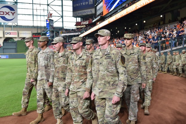 III Corps Soldiers march onto the baseball field at Minute Made Park in Houston, Texas to reenlist before a Houston Astros game on July 5, 2018.