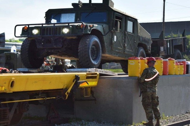 Illinois Army National Guard Soldiers drive a HUMMV onto the first car of an eight-car unit at the Rock Island Arsenal rail head July 10, 2018. More than 200 vehicles are being loaded at the Arsenal, with an additional 700 being loaded at Camp Atterbury, Indiana. The rail exercise is part of a movement by the ILARNG to the Joint Readiness Training Center at Fort Polk, Louisiana.
