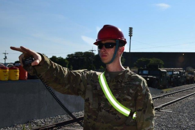 "Maj. Adam Malaty-uhr ""directs traffic"" as the loading proceeds a rail head at Rock Island Arsenal. Normally the executive officer of the 2nd Battalion, 106th Cavalry, Illinois Army National Guard, Malaty-uhr is lead on this weeks load-out at RIA."