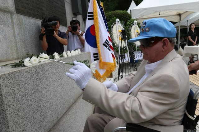 OSAN, Republic of Korea - Cpl. William Coe, a veteran of the Korean War and a member of Task Force Smith, places a flower at the TF Smith memorial, July 6, to commemorate the 68th anniversary of the first battle of the war involving U.S. Soldiers. TF Smith, comprised of a makeshift battalion of the Japan-based U.S. Army 24th Infantry Division, was sent to South Korea to delay the advance of North Korean forces. Inexperienced, understrength and ill-equipped, TF Smith sustained 60 killed, 21 wounded, and 82 captured, during its battle against North Korean forces. Nonetheless, TF Smith delayed the North's advance and reinforcements were eventually able to repel the invasion. (Photo by Staff Sgt. Todd Pouliot, 35th Air Defense Artillery Brigade)