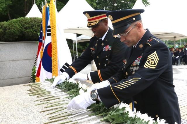 OSAN, Republic of Korea - Lt. Col. Matthew Walker and Command Sgt. Major Gene Harding, commander and command sergeant major, respectively, of 6th Battalion, 52nd Air Defense Artillery Regiment, 35th ADA Brigade, places flowers at the Task Force Smith Memorial, July 6, to commemorate the 68th anniversary of the first battle of the war involving U.S. Soldiers. TF Smith, comprised of a makeshift battalion of the Japan-based U.S. Army 24th Infantry Division, was sent to South Korea to delay the advance of North Korean forces. Inexperienced, understrength and ill-equipped, TF Smith sustained 60 killed, 21 wounded, and 82 captured, during its battle against North Korean forces. Nonetheless, TF Smith delayed the North's advance and reinforcements were eventually able to repel the invasion. (Photo by Staff Sgt. Todd Pouliot, 35th Air Defense Artillery Brigade)