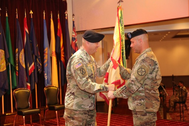 Command Sgt. Maj. Will Holland, left, passes the U.S. Army Garrison Japan guidon to Garrison Commander Col. Phillip Gage during Holland's relinquishment of responsibility ceremony July 11, 2018, at the Camp Zama Community Club. (U.S. Army photo by Noriko Kudo)